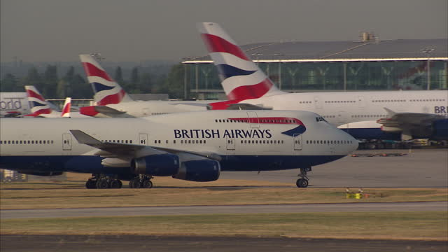 Exterior shots British Airways Boeing 747 passenger plane taxiing to runway at Heathrow airport with a British Airways Airbus A380 parked at terminal...