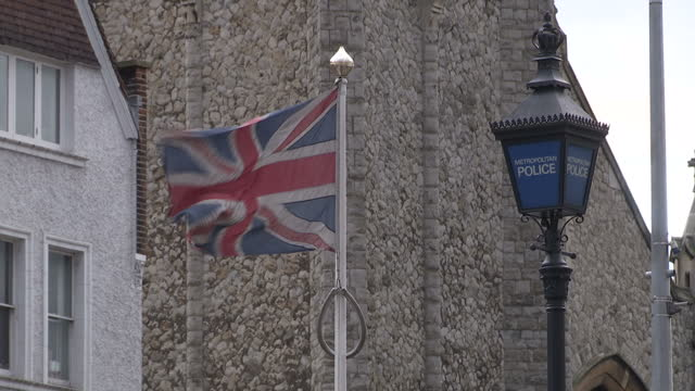 exterior shots british flag flying outside police station ext gv busy high street with cars and buses using roundabout - アラン・リックマン点の映像素材/bロール