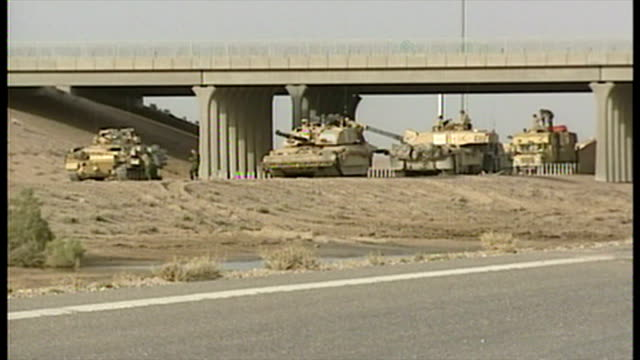 exterior shots british military challenger 2 tanks and apc's parked under bridge at side of road at the start of the 2003 invasion of iraq on march... - bassora video stock e b–roll