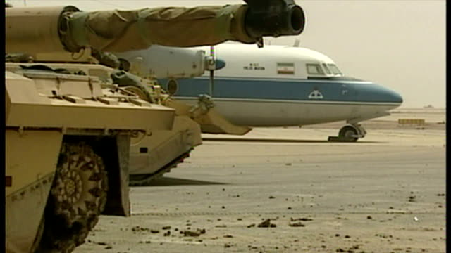 exterior shots british military challenger 2 tanks warrior apc vehicles on airport apron next to commercial planes at abandoned basrah international... - bassora video stock e b–roll
