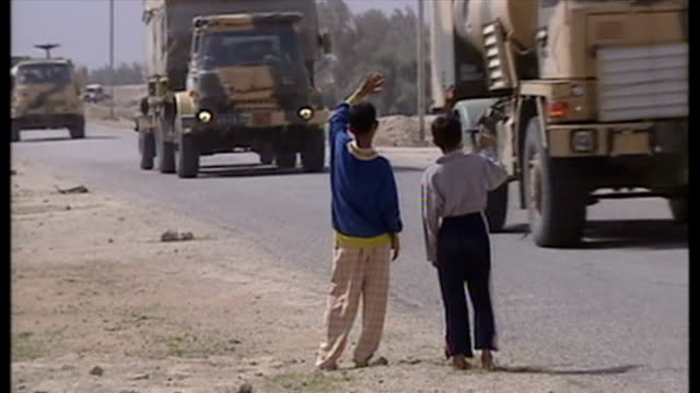 exterior shots british military convoy driving along road with 2 small children waving to convoy as armed british soldiers watch on at the start of... - british military stock videos and b-roll footage