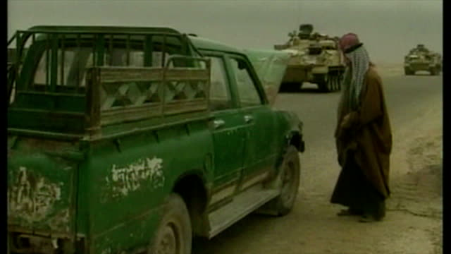exterior shots british military convoy passing along road past iraqi civilians standing next to broken down vehicle at the start of the 2003 invasion... - bassora video stock e b–roll