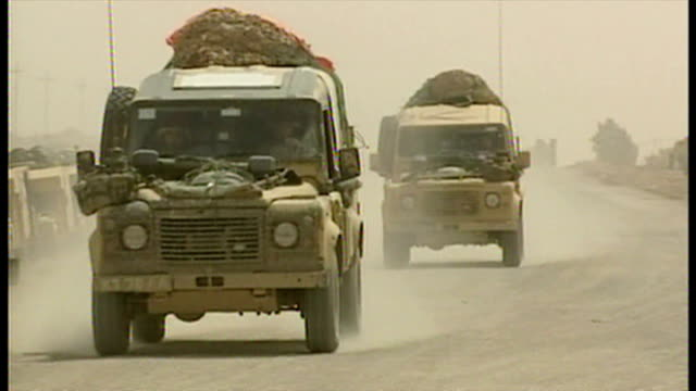 exterior shots british military vehicles passing through road checkpoint manned by british soldiers, at the start of the 2003 invasion of iraq. on... - british military点の映像素材/bロール