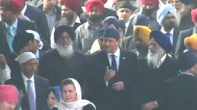 stockvideo's en b-roll-footage met exterior shots british prime minister david cameron lays wreath at 1919 massacre memorial and wearing turban during tour of golden temple hukamnama... - hoofdtooi