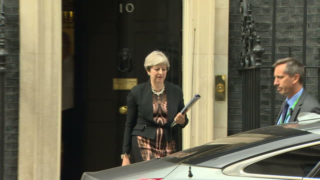 Exterior shots British Prime Minister Theresa May departing 10 Downing Street exits No 10 gets in car and drives off followed by police car in London...