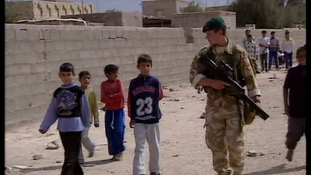 exterior shots british soldier on patrol walking along road being followed by iraqi children, at the start of the 2003 invasion of iraq. on march 29,... - iraq stock videos & royalty-free footage