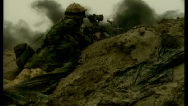 exterior shots british soldiers in muddy trenches aiming weapons over the top as oil fires rage in the distance at the start of the 2003 invasion of... - bassora video stock e b–roll