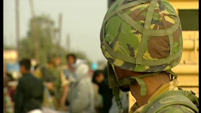 exterior shots british soldiers on patrol as other soldiers hand out water to iraqi civilians at the start of the 2003 invasion of iraq on march 29... - civilian stock videos & royalty-free footage