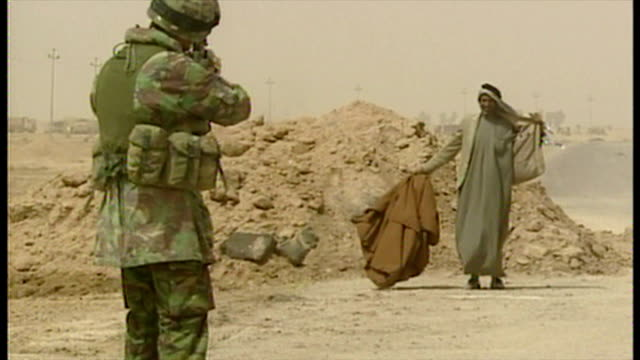 exterior shots british soldiers searching iraqi man at the side of the road looking for weapons at the start of the 2003 invasion of iraq on march 27... - bassora video stock e b–roll