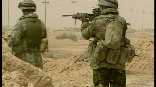 exterior shots british soldiers standing at road checkpoint looking through gun sights at the start of the 2003 invasion of iraq on march 27 2003 in... - british military stock videos & royalty-free footage
