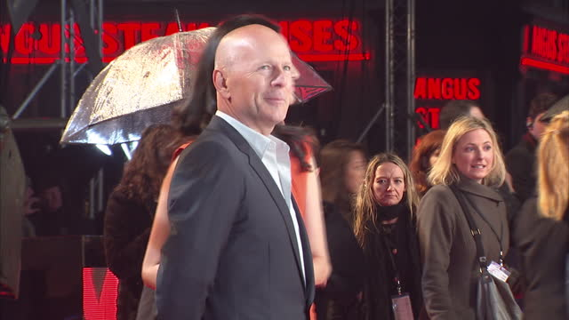 exterior shots bruce willis and emma heming posing on red carpet for press a good day to die hard film premiere at leicester square on february 07... - bruce willis stock-videos und b-roll-filmmaterial