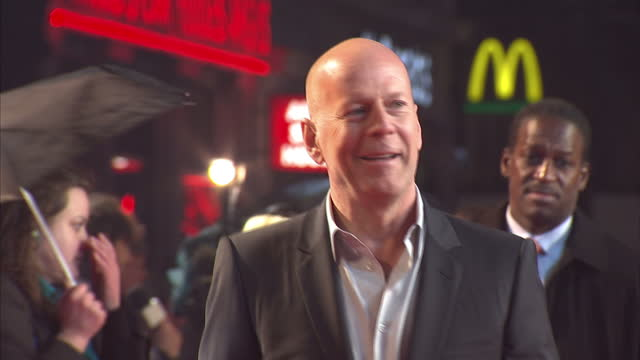exterior shots bruce willis arrives on red carpet and poses for press a good day to die hard film premiere at leicester square on february 07 2013 in... - bruce willis stock-videos und b-roll-filmmaterial