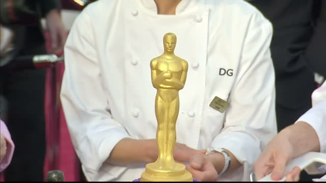 Exterior shots Celebrity Chef Wolfgang Puck stands with other chefs on the red carpet by large cake with Oscar statuette on top Oscar Chef Wolfgang...