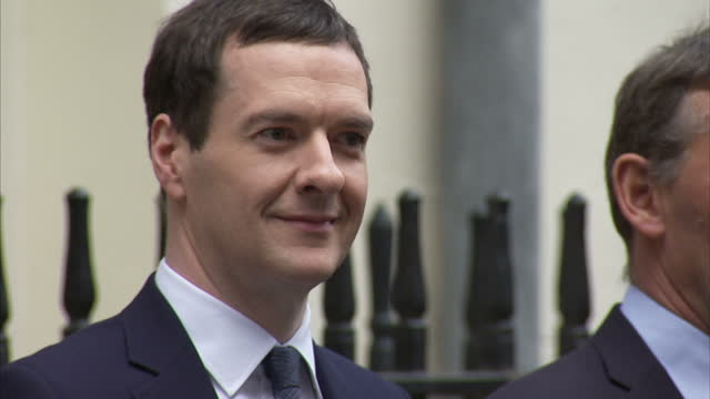 Exterior shots Chancellor George Osborne exits Downing Street No 11 and poses for photo op holding red Budget box on March 16 2016 in London England