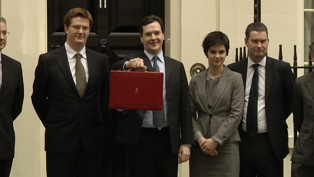 Exterior shots Chancellor George Osborne walks out from Number 11 Downing Street holding his red budget box flanked by members of his Treasury team...