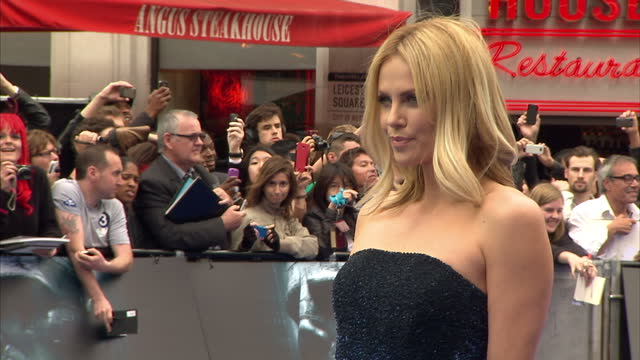 exterior shots Charlize Theron posing for photographers on blue carpet at Prometheus film premiere Charlize Theron at Prometheus Movie Premiere at...