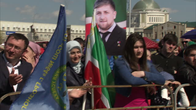 exterior shots chechen people chechens at peace day of chechen republic concert people listening to music holding portraits of vladimir putin and... - grosny stock-videos und b-roll-filmmaterial
