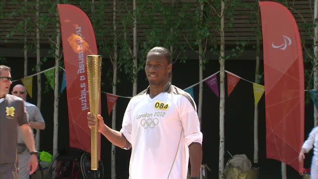 exterior shots chelsea footballer didier drogba poses holding flaming olympic torch before running with it didier drogba carries olympic torch in... - olympic torch stock videos & royalty-free footage