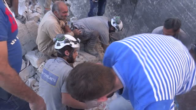 exterior shots child toddler being dug out from rubble by white helmets rescuers child laying in ambulance bed and ambulance on way to hospital with... - rubble stock videos & royalty-free footage