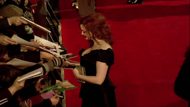 stockvideo's en b-roll-footage met exterior shots christina hendricks walks the red carpet signs autographs at the bafta 2012 arrivals christina hendricks on the bafta red carpet on... - signeren