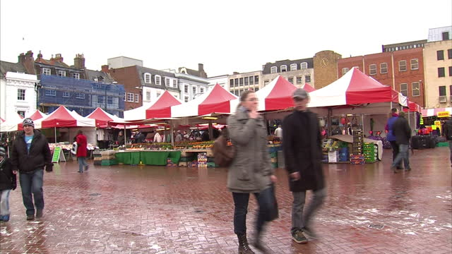 vidéos et rushes de exterior shots christmas market square with shoppers browsing & looking through market stalls. exterior shots father christmas arrives on motorised... - northampton