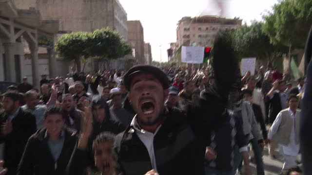 vídeos de stock, filmes e b-roll de exterior shots civilian militia anti gaddafi rebels march and chant holding guns in the street rebels still in control of zawiyah on march 08 2011 in... - líbia
