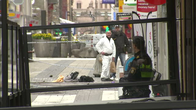 exterior shots crime scene with police officers stood guard behind cordon tape police forensics wearing white boiler suits and holding evidence bags... - terrorism bildbanksvideor och videomaterial från bakom kulisserna