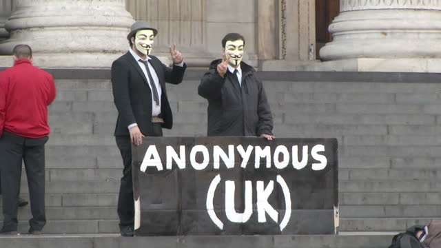 exterior shots crowd of protesters camped on the steps of st paul's cathedral. exterior shots protesters in guy fawkes masks hold banner. exterior... - occupy protests stock videos & royalty-free footage