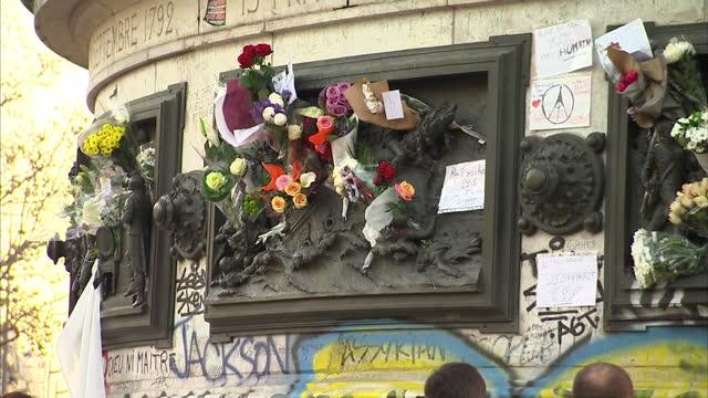 vidéos et rushes de exterior shots crowds looking at floral tributes & chalk messages in place de la republique in memory of victims of paris terror attacks on november... - victime