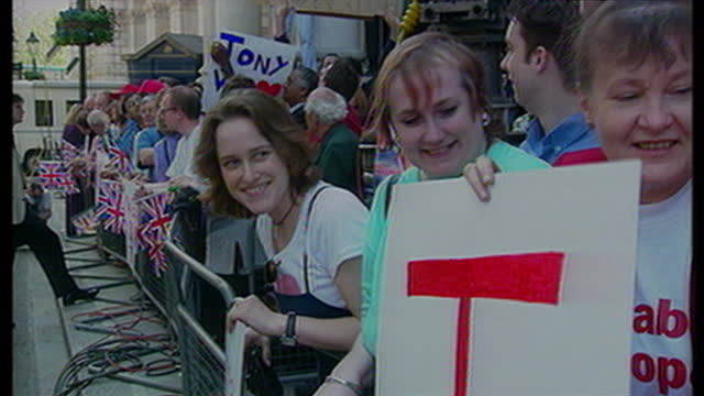 exterior shots crowds of labour supporters waiting with banners for tony blair's arrival at downing st. on may 2nd, 1997 in london, united kingdom. - コベントリー点の映像素材/bロール