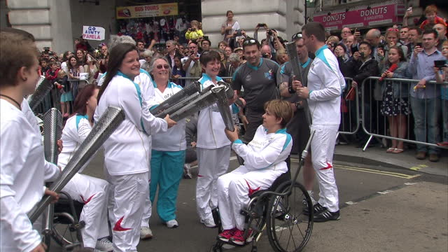 exterior shots dame tanni greythompson lights paralympic torch with the aide of other torch bearers carries it in wheelchair past cheering crowds... - flaming torch stock videos & royalty-free footage
