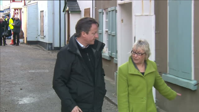 exterior shots david cameron british prime minister being show around town damaged by flooding and storm waves which battered the sea front on in... - kingsand video stock e b–roll