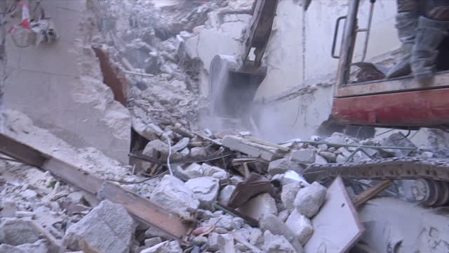 Exterior shots digger and crews clearing rubble away aftermath of airstrike on September 30 2016 in Aleppo Syria