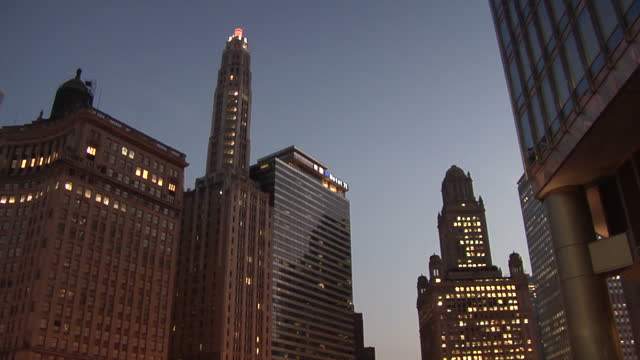 exterior shots downtown chicago at dusk with traffic travelling across michigan avenue bridge exterior shot us flag flying on building exterior shots... - michigan avenue bridge stock videos and b-roll footage