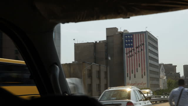 exterior shots driving through tehran, including new construction underway, murals of the ayatollah khomeini and a 'down with the usa' mural. on july... - combustibile fossile video stock e b–roll