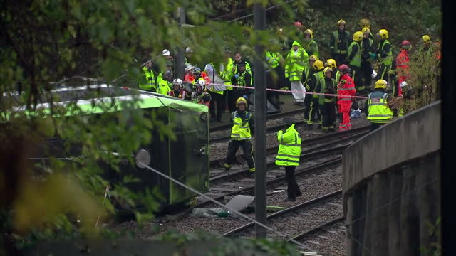exterior shots emergency services at scene of tram derailment with workers standing on tracks next to overturned tram. on november 09, 2016 in... - ロンドン クロイドン点の映像素材/bロール