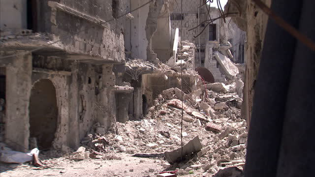 exterior shots empty dusty streets in south damascus bullet holed tower ruin street filled with rubble and debris no windows or doors and evidence of... - rubble stock videos & royalty-free footage