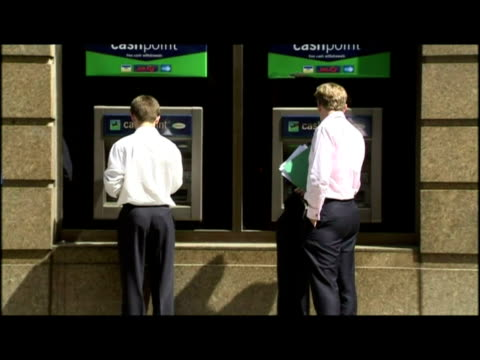 exterior shots evening standard news board headline ' profit crash rocks banks ' exteriors anon people using lloyds tsb atm cash machine cash point - 2008 stock videos and b-roll footage