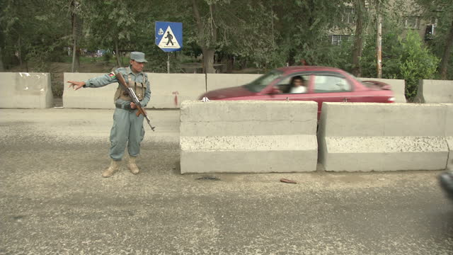 Exterior shots ext gvs Afghan policeman stood in road with gun as cars pass on September 07 2012 in Kabul Afghanistan