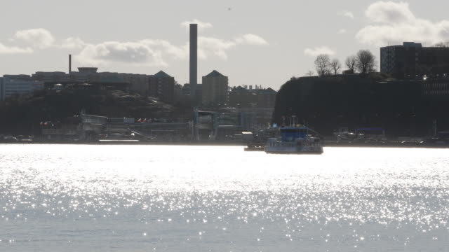 exterior shots ferries crossing stockholms ström with the sun reflecting off water on 3 april 2020 in stockholm, sweden - stockholm stock videos & royalty-free footage