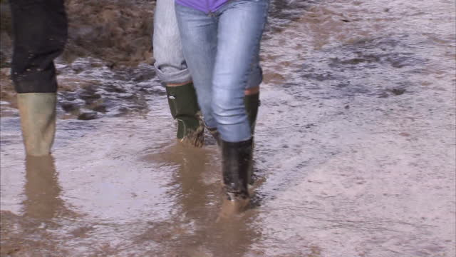 stockvideo's en b-roll-footage met exterior shots festival goers walk through expansive area of mud at the isle of wight festival people walk through mud at festival on june 23, 2012... - rubberlaars