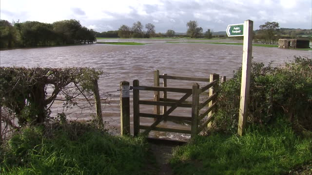 exterior shots fields and park land flooded after storm. public footpath signage with flood waters in background. 99 mph winds and heavy downpours... - devon stock videos & royalty-free footage