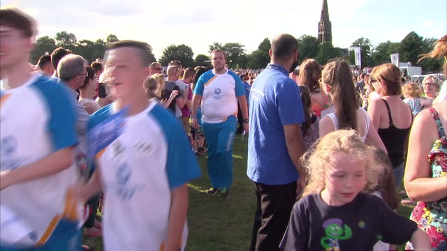 exterior shots final stop of baton relay, crowds cheering runners and baton on stage, exterior shots crowds gathered in sun outside commonwealth... - commonwealth games stock videos & royalty-free footage