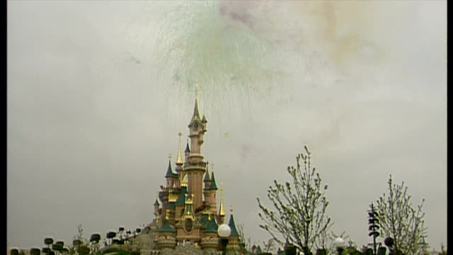 exterior shots fireworks in front of the disney sleeping beauty castle as euro disney resort opens and crowds of waiting tourists are let into the... - disney stock videos and b-roll footage