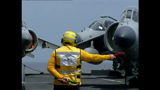 exterior shots flight deck and operations crew on flight deck of hms illustrious preparing royal navy sea harrier fighter jets for takeoff during... - hospital corpsman点の映像素材/bロール