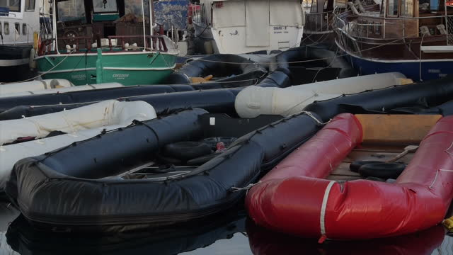 KOS exterior shots flotilla of abandoned migrant inflatable boats in harbour / inflatable dinghy w/ Yamaha outboard engine