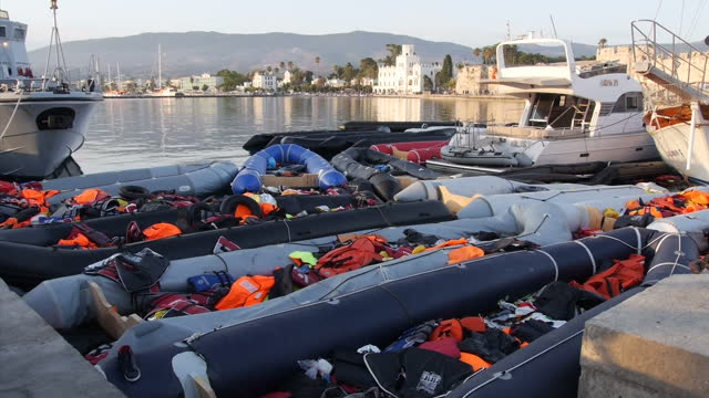 KOS exterior shots flotilla of refugees inflatable boats in port many deflated and strewn with life jackets