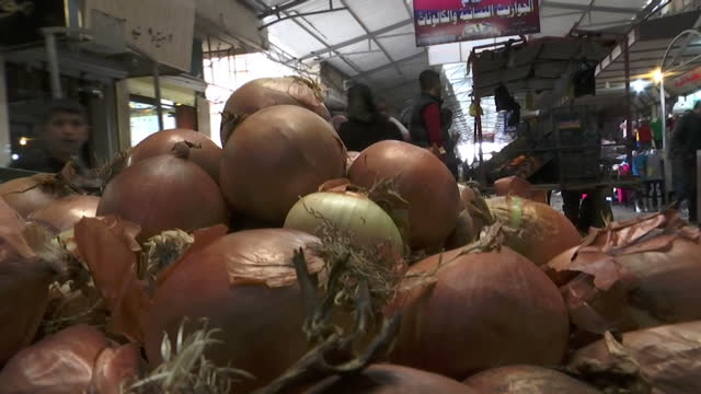 Exterior shots following a market trader wheeling a cart of onions through a busy Mosul market on 24 March 2017 in Mosul Iraq
