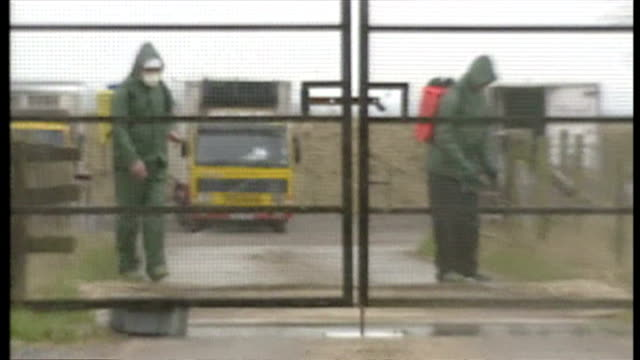 exterior shots foot and mouth warning sign at entrance, taped off farm area, exterior shots men wearing protective clothing and masks spraying... - wiltshire stock videos & royalty-free footage