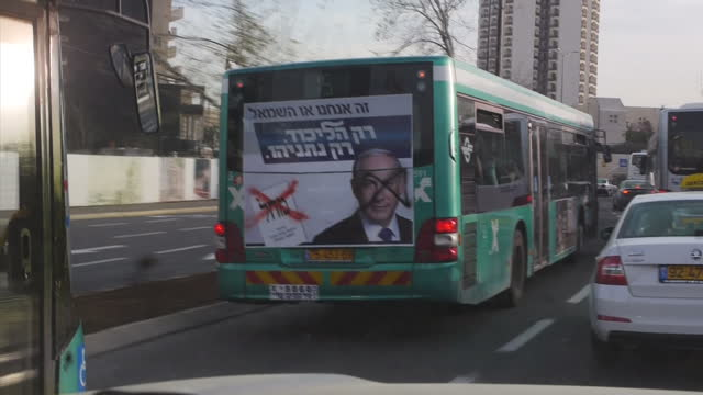 exterior shots from a moving car in traffic of a bus in ashkelon carrying a poster for likud party candidate binyamin netanyahu with graffiti... - ashkelon stock videos and b-roll footage